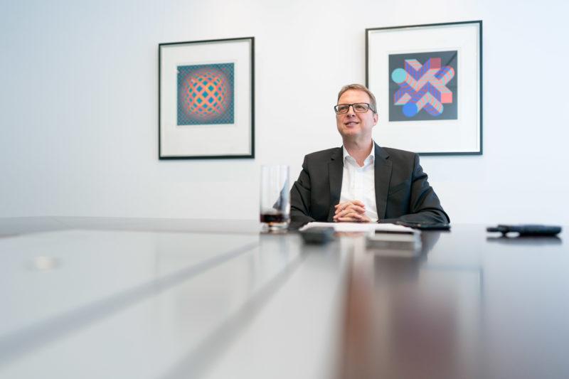 Portraitfotografie - Portrait eines Managers einer großen Softwarefirma: Das verwendete Weitwinkelobjektiv schafft Raum und ermöglicht die Nutzung von Spiegelungen im Tisch, an dem die Person sitzt.