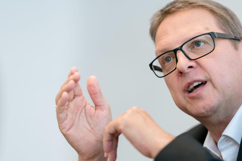 Portraitfotografie - Portrait eines Managers einer großen Softwarefirma: Mit Teleobjektiv aufgenommenes nahes Portrait eines Ausschnitts der Kopfes und gestikulierenden Händen.