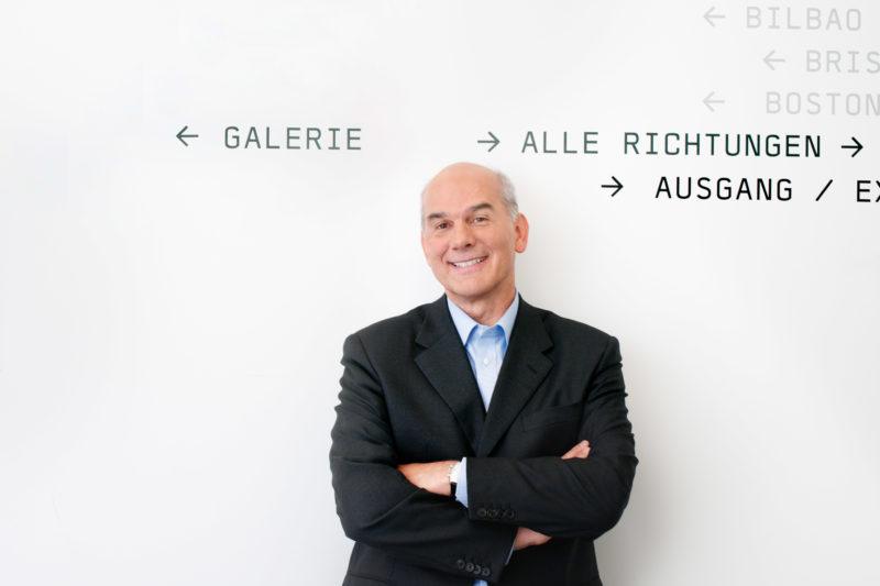 Eventfotografie, Veranstaltungsfotografie Reportagefotografie: Businessportrait: Portrait eines Managers im Flur seiner Firma vor einer weisser Wand mit Wegweisern.