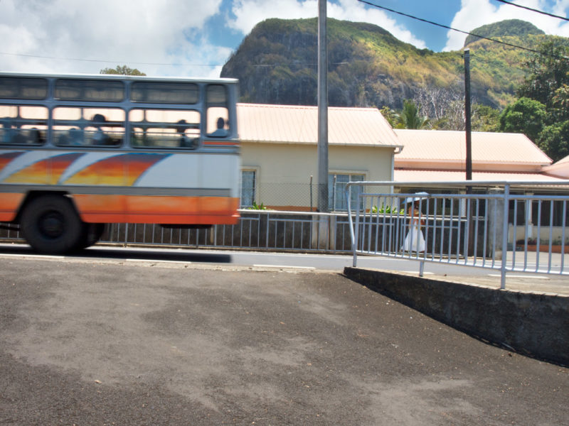 travel photography: Mauritius: A woman with a parasol after getting off one of the intercity buses.