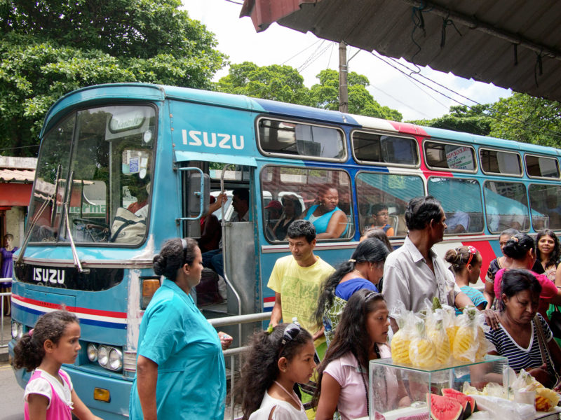 travel photography: Mauritius: Faces and a fashion doll at a full bus station on a main road.