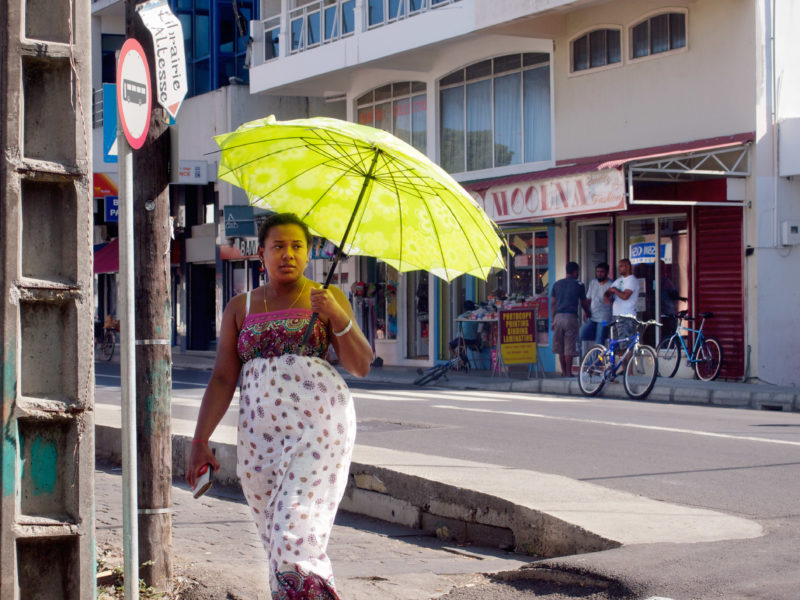 travel photography:  Mauritius: A woman with a green parasol walks on the street of a small town. Behind her is a clothing fashion store.