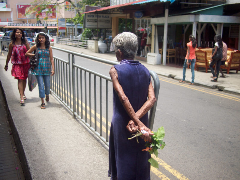 travel photography: Mauritius: An elderly woman with herbs in her hand between young ladies on a main road.