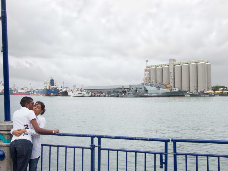 travel photography: Mauritius: Lovers at the pier in the port of Port Louis. In the background ships of the coast guard.