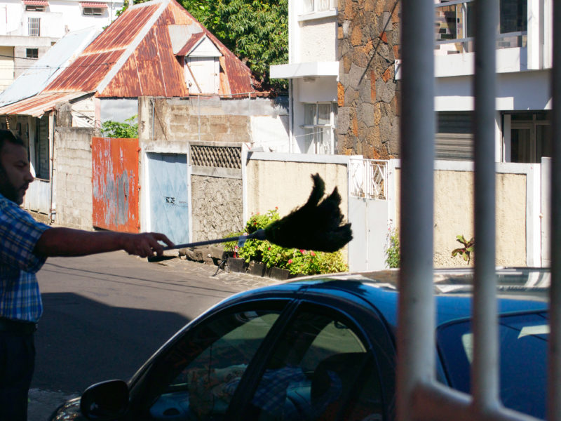 travel photography: Mauritius: A man dusts his car with a big duster.