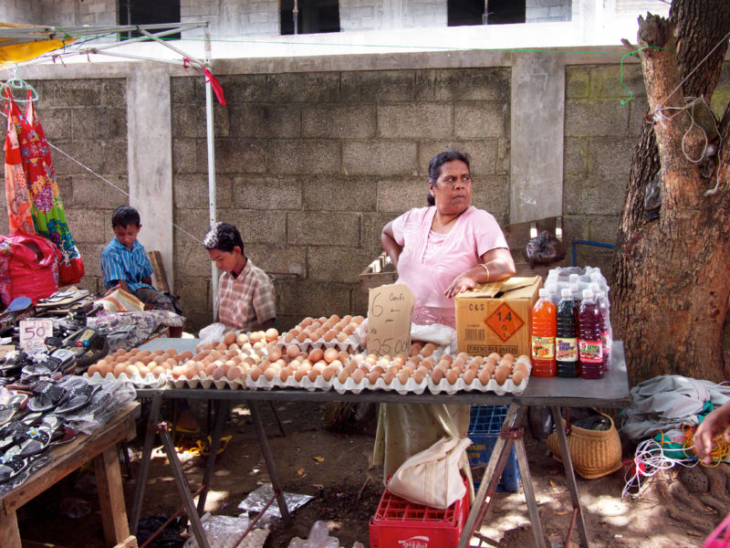 travel photography: Mauritius: Children and a seller of eggs and drinks at her stand at a small street market.