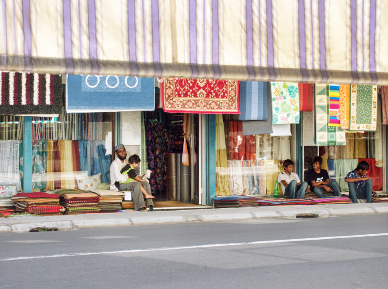 travel photography: Mauritius: A carpet and cloth merchant with children in front of his shop.