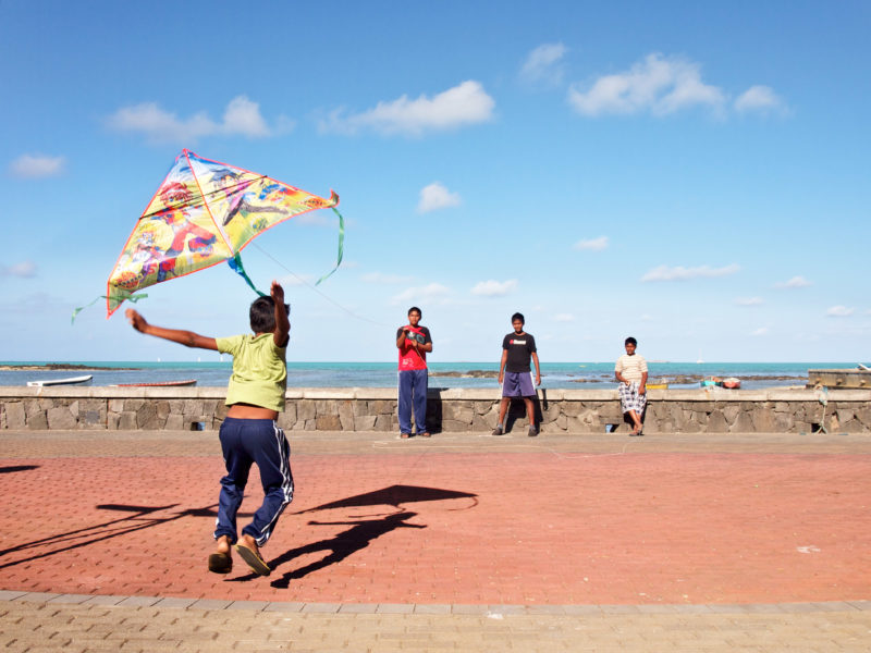travel photography: Mauritius: Children play with a paper kite in the wind at the beach promenade of Grand Port.