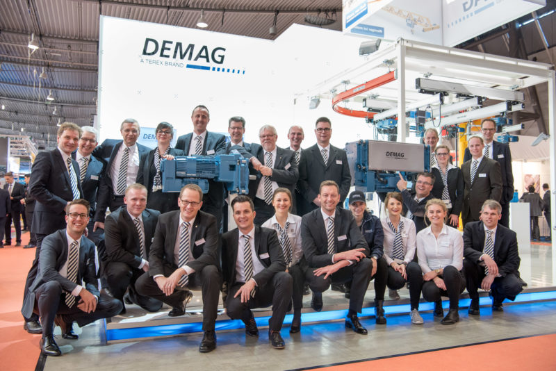 Group photo: Stand personnel of an exhibition stand in front of their brightly lit exhibition stand.