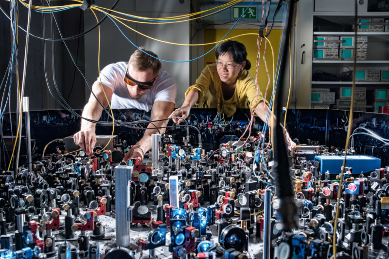 Science photography: 2 employees at a measuring table of the 5th Physical Institute of the University of Stuttgart under the direction of Prof. Dr. Tilman Pfau. The table is covered with optical modules that conduct laser light and sensors that make measurements possible.