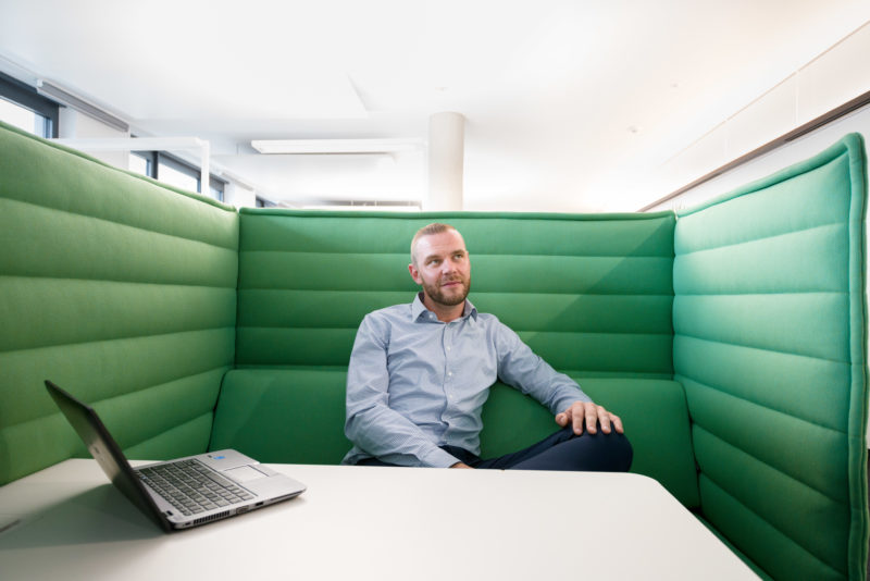 Employees photography: An employee sits in a modern office in a meeting corner covered with green fabric.