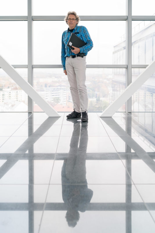 Employees photography: An employee of a software company on a corridor in the high-rise of the company building. The large glass surfaces provide a view of the city while the man is reflected in the shiny floor tiles.