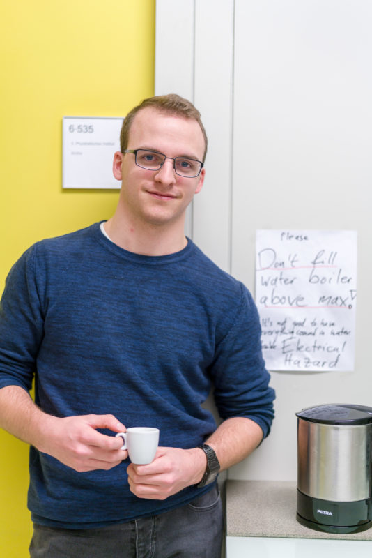 Science photography: An scientist of a physical institute in the coffee kitchen at a university. He has an espresso cup in his hand, while one of them is holding a kettle and a handwritten warning sign against the electric dangers of boiling over.