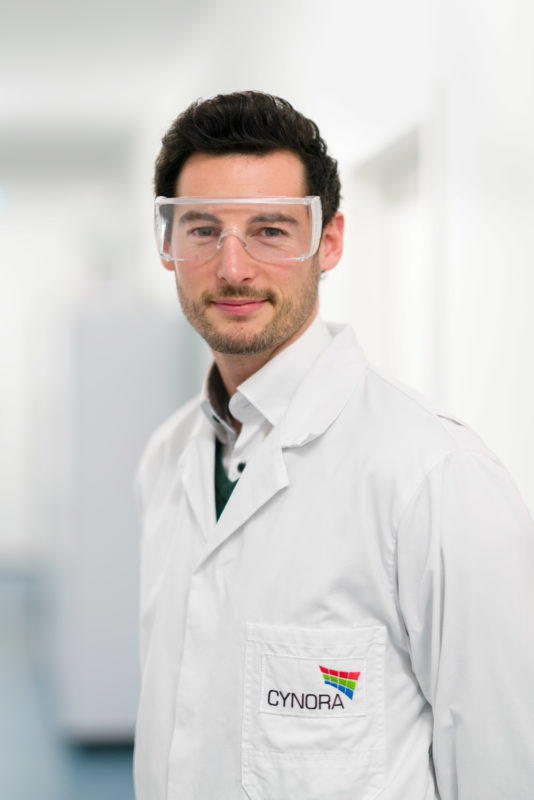 Employees photography:  An employee in the laboratory of a company researching luminescent materials for OLED production. He wears protective goggles.
