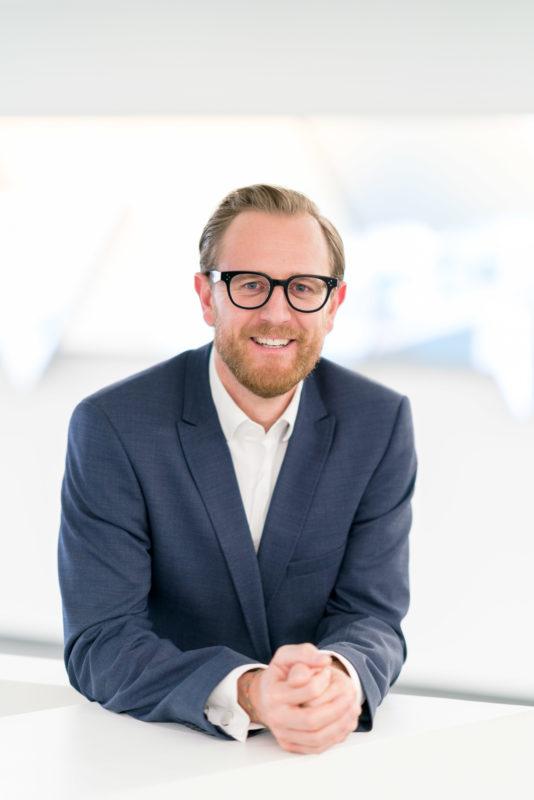 Managerportrait: Ein Firmenmitarbeiter steht aufgelehnt an einem weissen Tisch und lächelt in die Kamera. Alles ist weiss und damit hell und freundlich. Er trägt ein blaues Jacket ohne Krawatte.