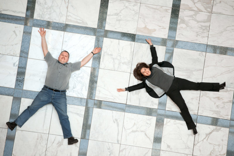 Employees photography: Employees Portrait: Two employees are on the floor laughing and form an X.