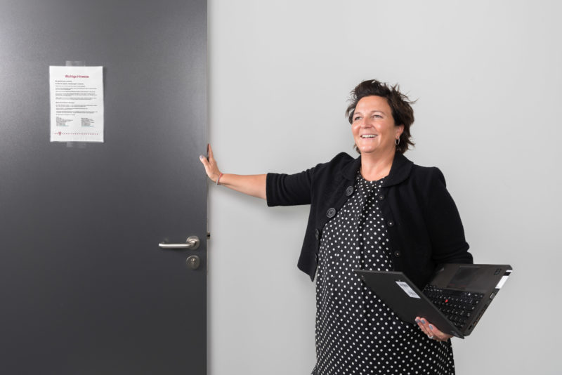 Employees photography: An employee with an opened notebook in her hand in the hallway of her company. She laughs as she opens a door.