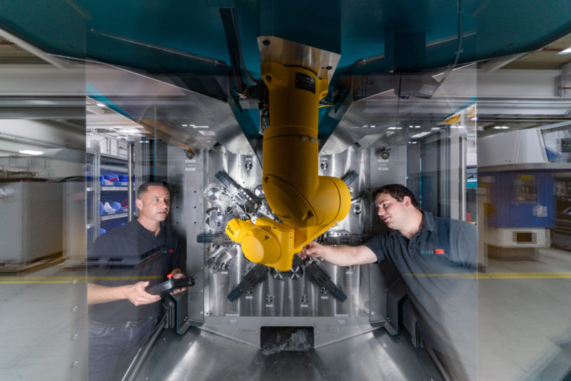 Industrial photography:  Employees testing a yellow robot arm in a new machine tool.
