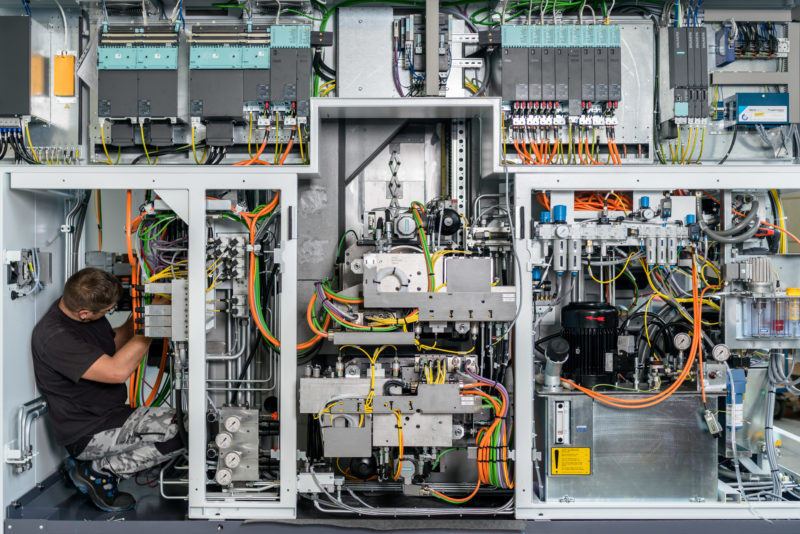 Industrial photography: When manufacturing a machine tool, the employee almost disappears between the many cables and metal parts of the machine.