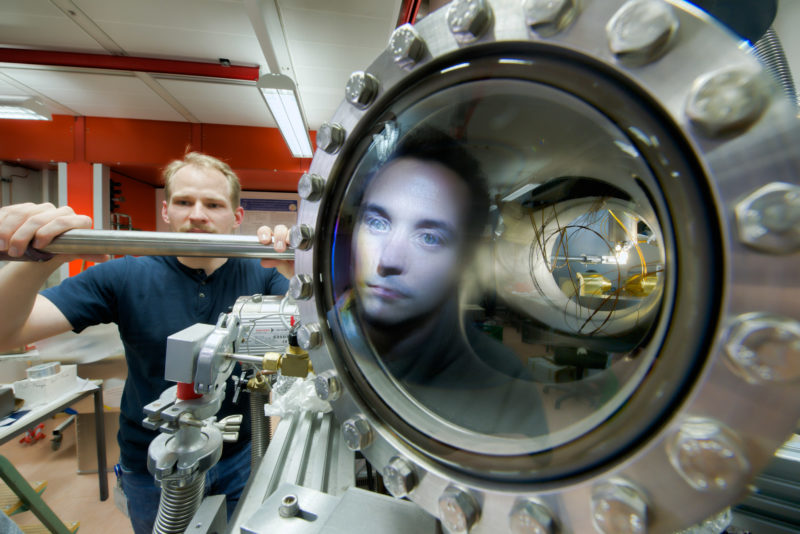 Science photography: An employee is mirrored in a glass seal during the preparation of an experiment in a vacuum chamber in the Department of Modern magnetic systems of the Max Planck Institute for Intelligent Systems in Stuttgart.