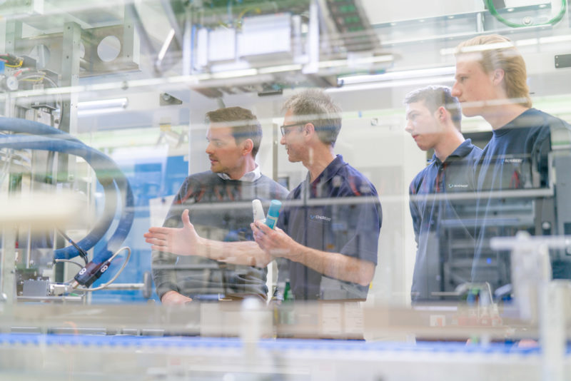 Industrial photography: Four employees at a medium-sized manufacturer of packaging machines discuss details on one of their systems.