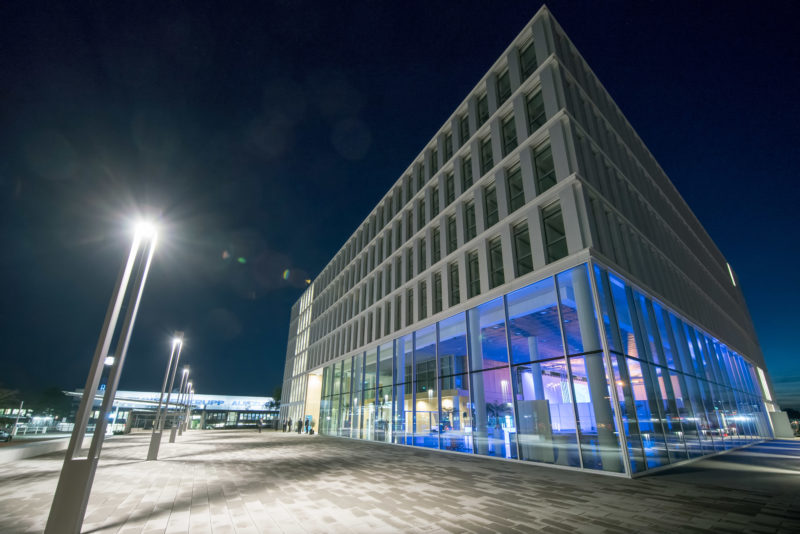 Architectural photography: Night shot of a company headquarters illuminated in blue in the foyer from the outside.
