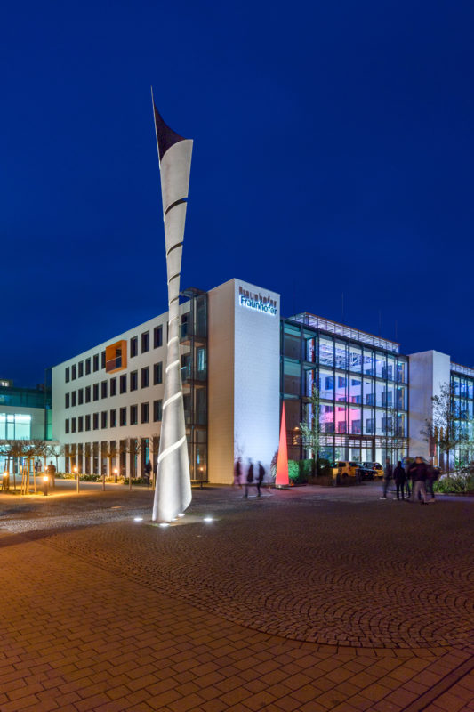 Architectural photography: Nightly illuminated building of the Fraunhofer Institute for Industrial Mathematics ITWM in Kaiserslautern with a high helically formed metallic plastic in front of it.