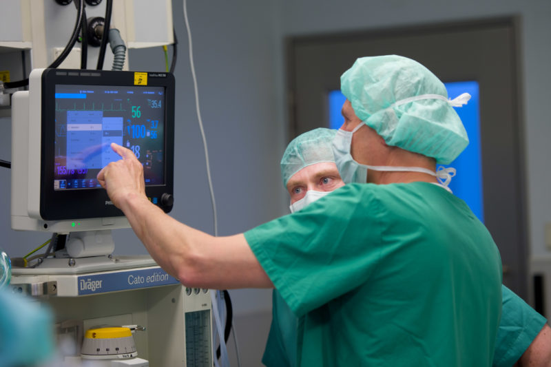 Healthcare photography:  In the operating theatre, a doctor operates the touch screen of an anaesthesia device while a surgeon talks to him.