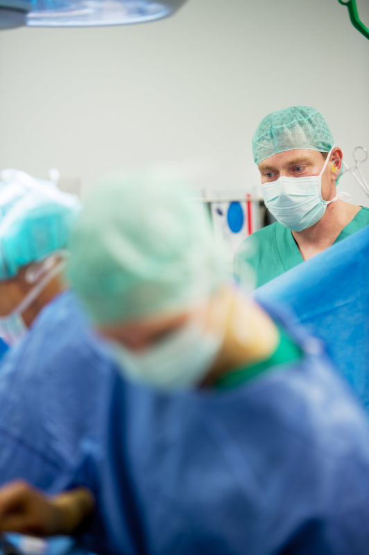 Healthcare photography: A doctor observes the course of an operation. Like everyone else in the operating room, he wears a mask and a green hood.