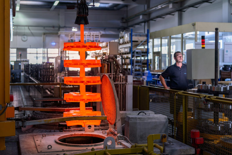 Industrial photography: By crane, an employee lifts raw metal parts, glowing in orange, out of the furnace.