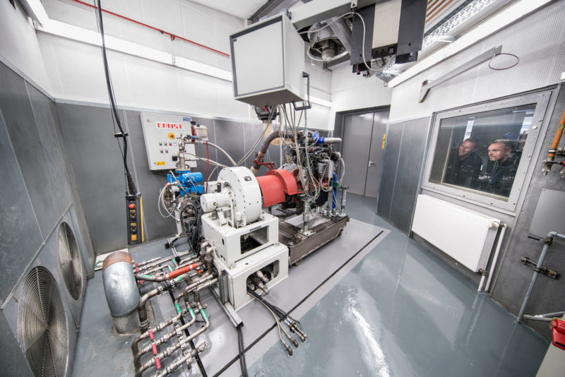 Industrial photography: Panorama photo of the interior of an engine test bench. The motor is connected to a braking device so that its power can be measured. Two employees look at the combustion engine from the steering position through the double safety glass pane.