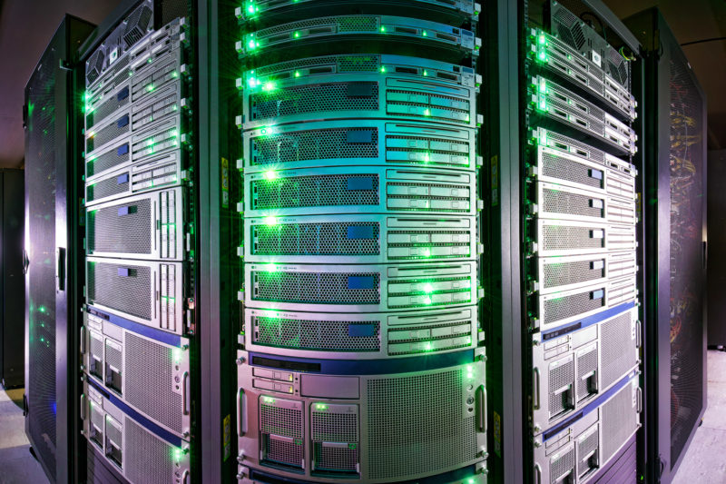 Industrial photography: Green illuminated server cabinet in a data center. The picture is taken in panorama technique to show the whole width of the servers standing next to each other.