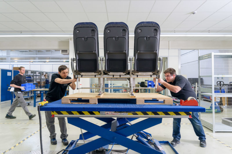 Industrial photography: At a manufacturer of passenger seats for aircraft, 3 seats are assembled on a lift table to form part of a row of seats for the cabin.