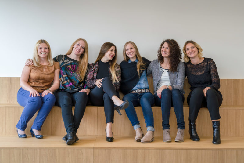 Group photo: Six members of a human resources department sit together on a bench in their company and are happy.