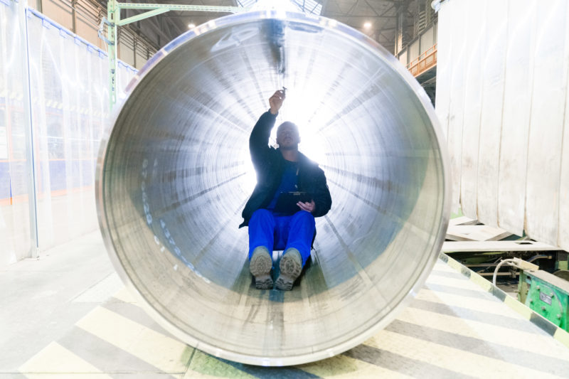 Industrial photography: In order to check the longitudinal weld seam of a pipe for a gas pipeline at a manufacturer of large steel pipes, an employee drives through the pipe on a rolling seat.
