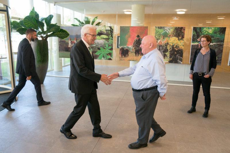 Fotoreportage - Besuch des Ministerpräsidenten bei einer mittelständischen Firma: Winfried Kretschmann begrüßt bei der Ankunft im Foyer als erstes den Seniorchef der Firma.