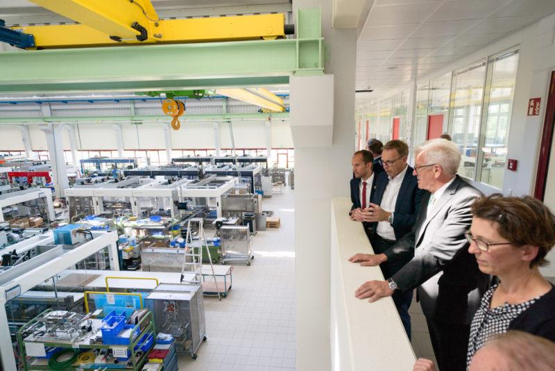 Fotoreportage - Besuch des Ministerpräsidenten bei einer mittelständischen Firma: Die Besuchergruppe steht auf einer Galerie und kann so eine der Produktionshallen überblicken.