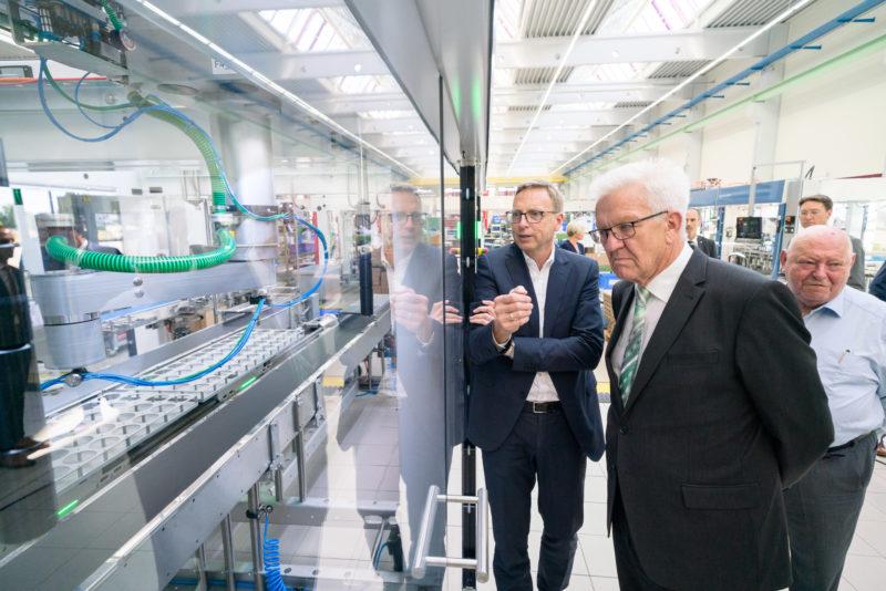 Fotoreportage - Besuch des Ministerpräsidenten bei einer mittelständischen Firma: Während dem Rundgang durch die Produktion werden Details einer Maschine erklärt.