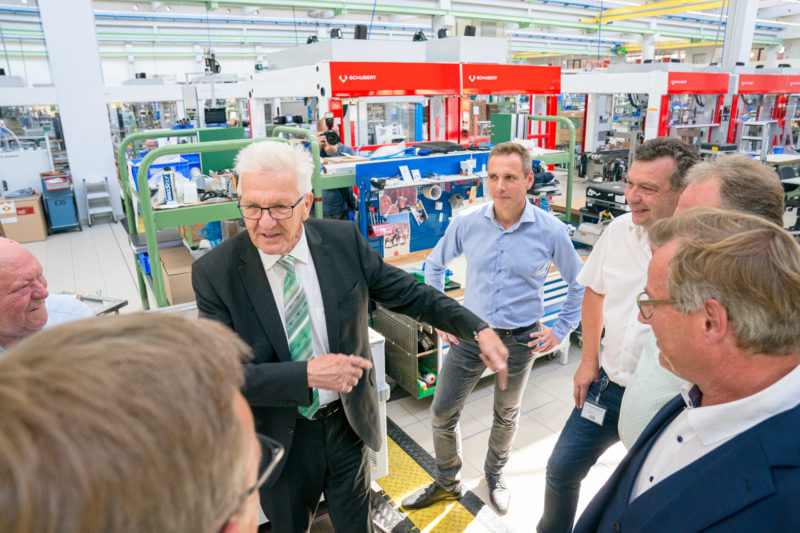 Editorial photography - Visit of the Prime Minister to a medium-sized company: Stop at one of the machines. Minister President Winfried Kretschmann talks to the people who serve them.