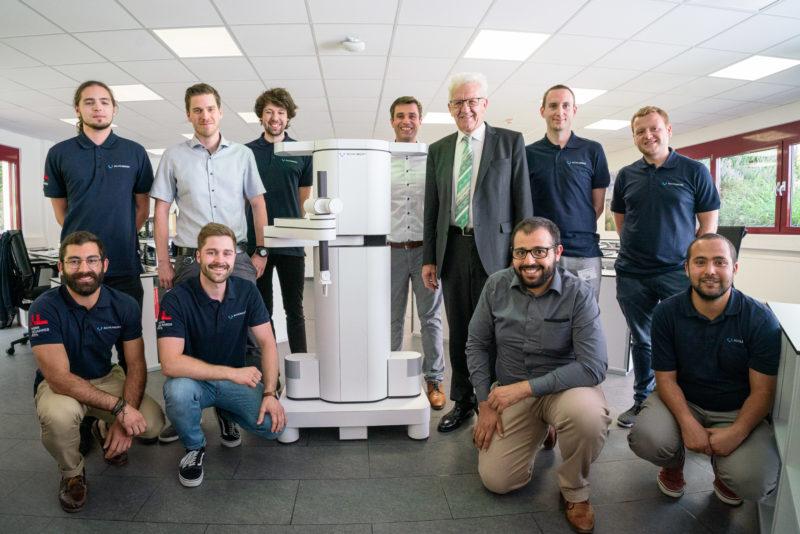 Fotoreportage - Besuch des Ministerpräsidenten bei einer mittelständischen Firma: Gruppenbild an einem Modell eines Roboters.