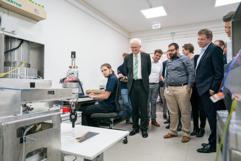 Fotoreportage - Besuch des Ministerpräsidenten bei einer mittelständischen Firma: Vorführung eines Roboterarms im Entwicklungslabor.