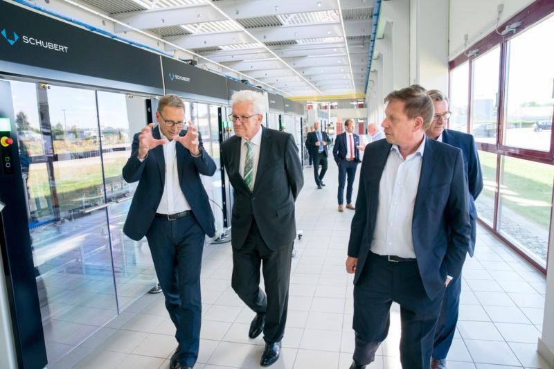 Fotoreportage - Besuch des Ministerpräsidenten bei einer mittelständischen Firma: Während des Rundganges durch die Produktion im Rückwärtsgehen fotografiertes Bild.