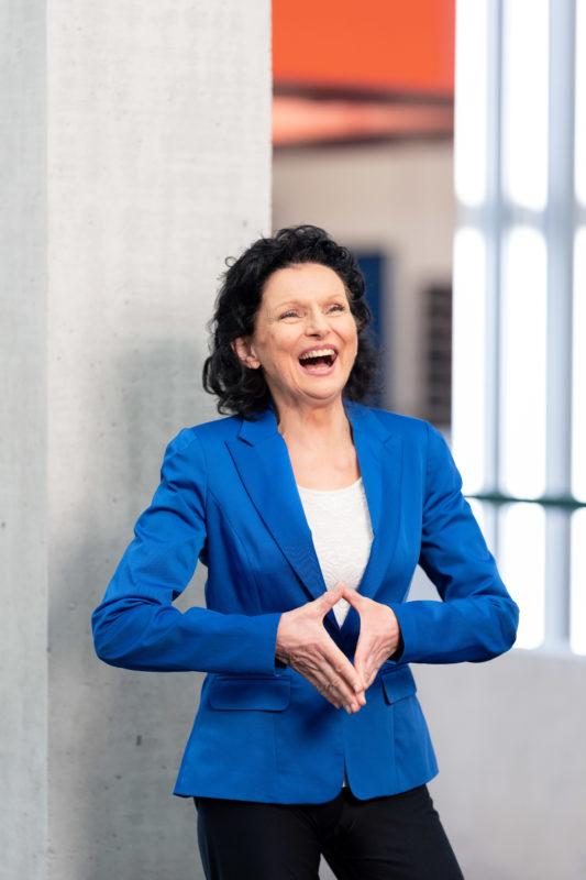 Portraitfotografie: Wissenschaftler in ihrem Institutsgebäude. Manchmal sind die spontanen Gesten die schönsten. Hier lacht die Portraitierte und hält die Hände wie die Bundeskanzlerin.