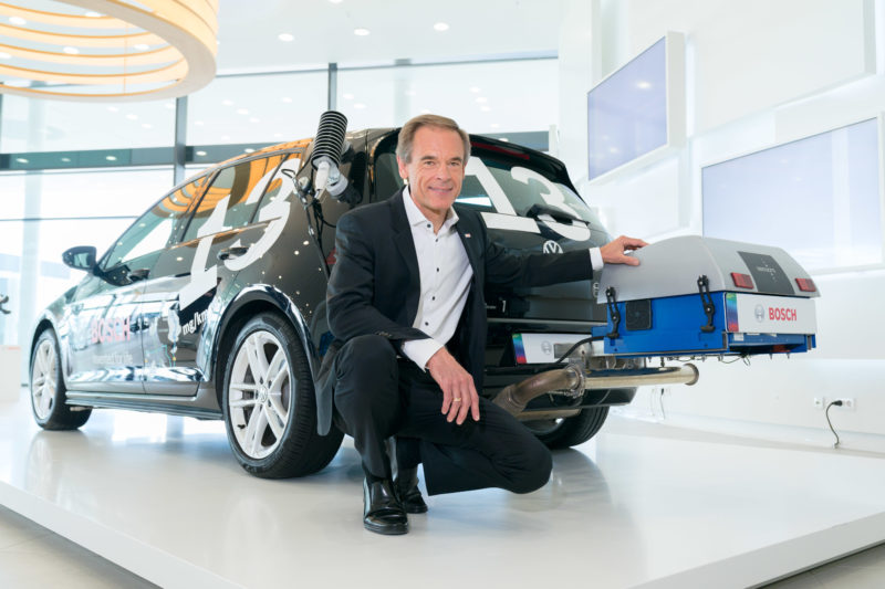 editorial photography: Press conference of Robert Bosch GmbH: Board of Management member Dr. Volkmar Denner poses in front of a very environmentally friendly diesel vehicle. An emission measuring device is mounted at the rear.