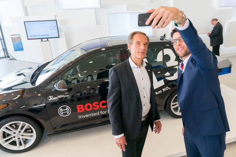 PR photography: Press photos at the press conference of Robert Bosch GmbH: Board of Management member Dr. Volkmar Denner and an associate make a selfie in front of an environmentally friendly diesel vehicle.