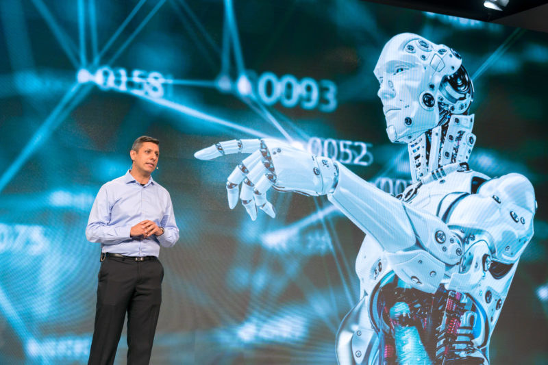 PR photography: Press photos at the press conference of Robert Bosch GmbH: An associate making a statement. A humanoid robot is shown in the background.