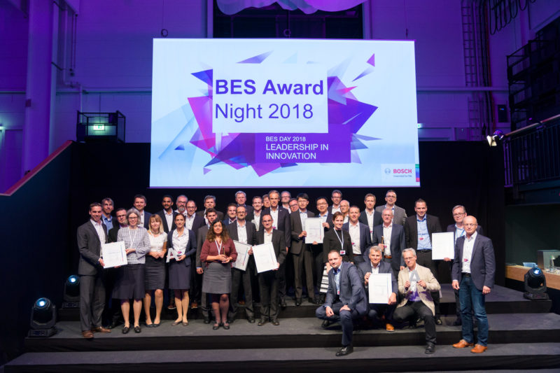 Group photo: After an award ceremony at a company event, all prize winners stand and sit together for a group photo. Above the logo of the event.