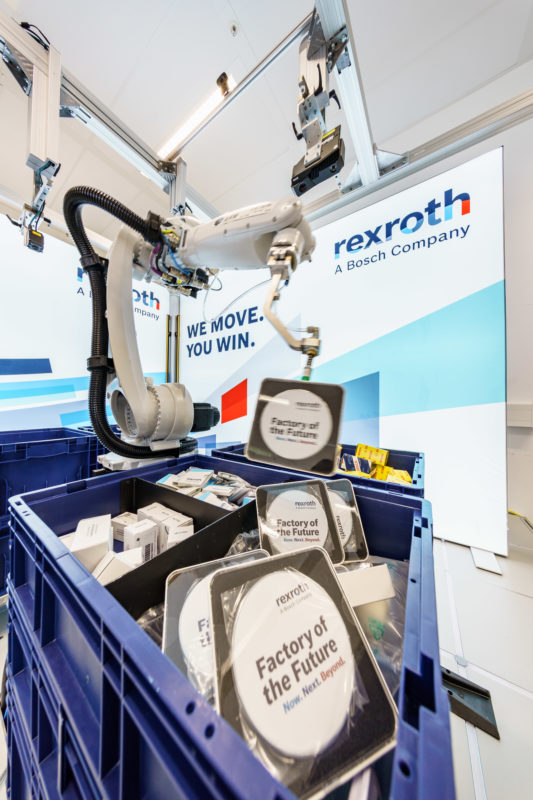 Press photo industry: Industrial robot that can grip disordered materials from boxes. You can see how the gripper lifts a product out of a box, on which other products are lying disordered in it.