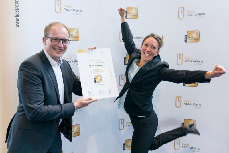 Event photography, editorial photography: After an award ceremony, a winner jumps up in cheers for the press photo, while her colleague holds the award certificate in the picture.
