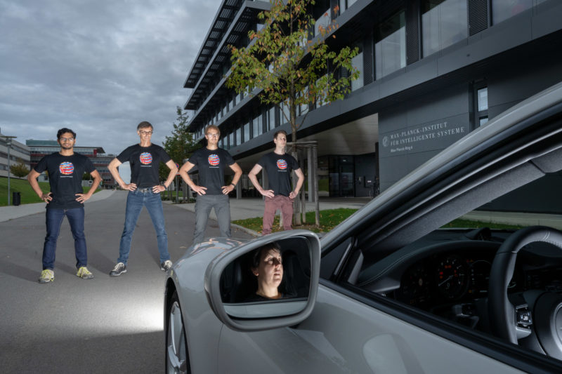 Press photo: A small colour pattern can disturb autonomously driving cars. A research team is standing in front of a vehicle. They are wearing T-shirts with this pattern they have developed. In the exterior mirror you can see the driver.